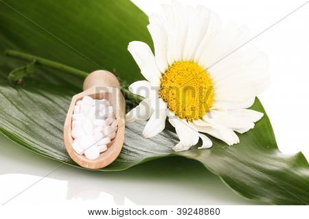 homeopathic tablets and flower on green leaf isolated on white