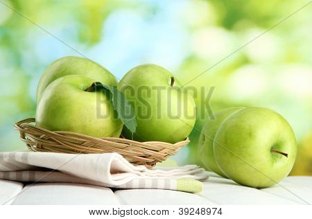 Ripe green apples with leaves in basket, on wooden table, on green background