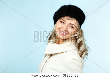 mid adult happy smiling woman winter portrait, attractive caucasian middle aged 40 years old lady in coat and hat over blue