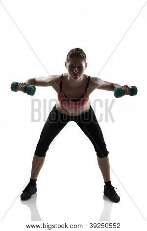 sport young athletic woman doing exersise with dumbbells, silhouette studio shot over white background