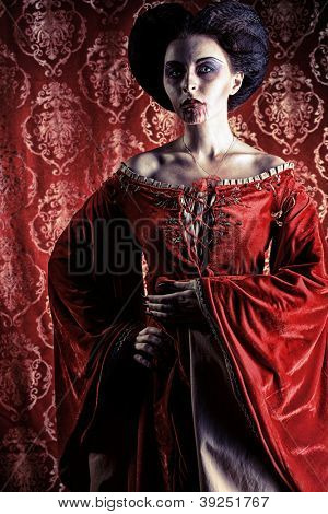 Portrait of a beautiful female vampire over red vintage background.