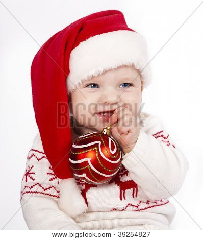 baby in Santa hat holding Christmas decorations in hand