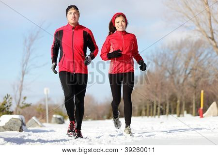 Running. Runners exercising in winter. Male and female runner training for marathon. Healthy lifestyle image with interracial active couple jogging in snow.  Asian woman, Caucasian man.