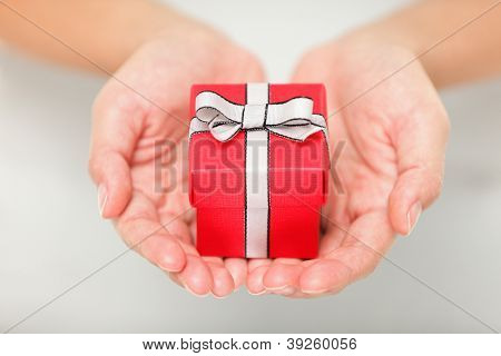 Gift. Woman holding showing gift or christmas gift in her hands. Female hands giving red present.