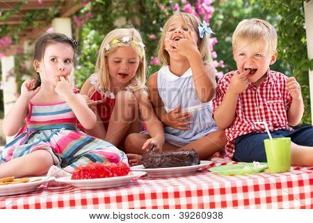 Group Of Children Eating Jelly And Cake At Outdoor Tea Party