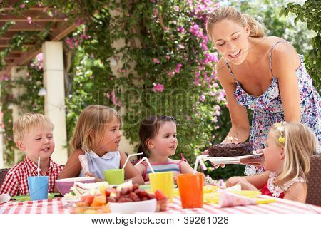 Mother Serving Birthday Cake To Group Of Children Outdoors