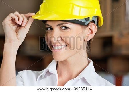 Portrait of an attractive female supervisor touching yellow hardhat at warehouse