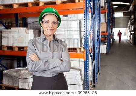 Portrait of young female supervisor wearing protective eyeglasses with arms crossed at warehouse
