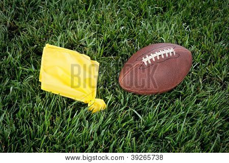 A yellow penalty flag and football lie motionless on a playing field.
