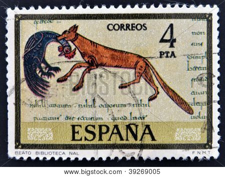 SPAIN - CIRCA 1975: A stamp printed in spain shows fox eating up rooster drawing national library ci