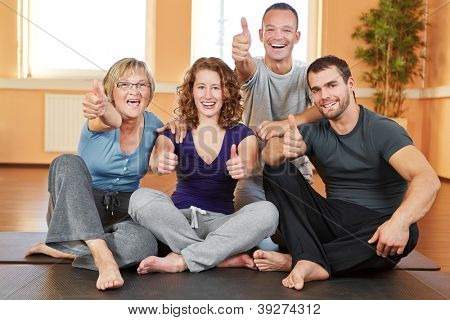 Cheering happy fitness group holding their thumbs up in a gym