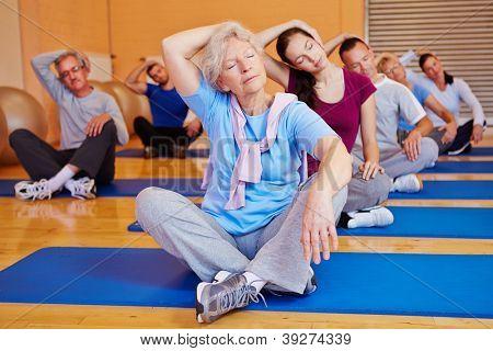 Fazer alongamentos nas costas formação classe em um centro de fitness do grupo