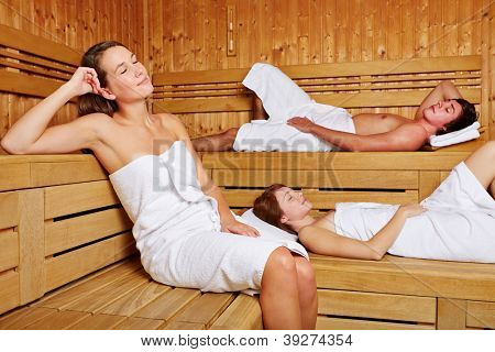Three young people sitting relaxed in a sauna