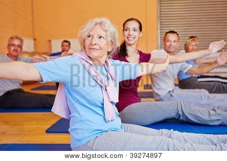 Senior woman doing gymnastics exercises in back training course in gym