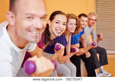 Happy group lifting dumbbells in a fitness center gym