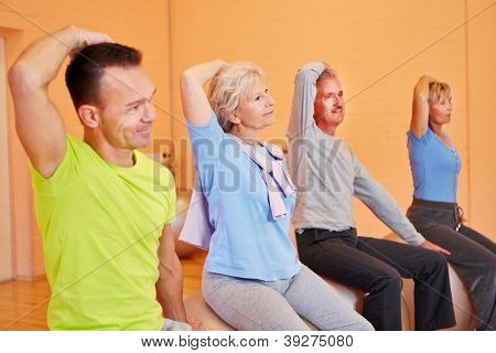 Group of senior people exercising in gym on fitness balls