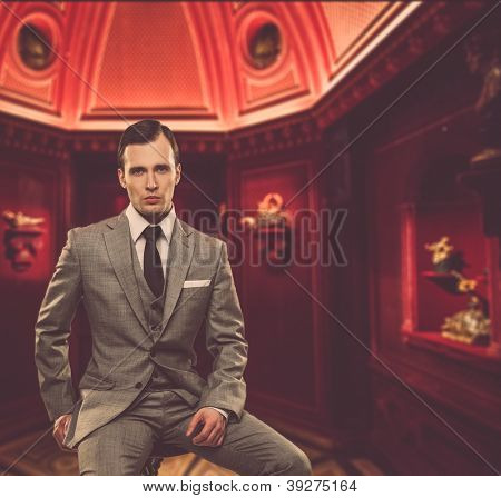 Confident man in classic grey suit sitting on chair in cabinet