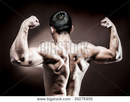 muscular male back on dark background