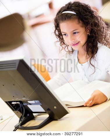 Young schoolgirl working on a computer at school