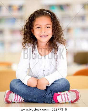 Happy schoolgirl at the library sitting on top of a table
