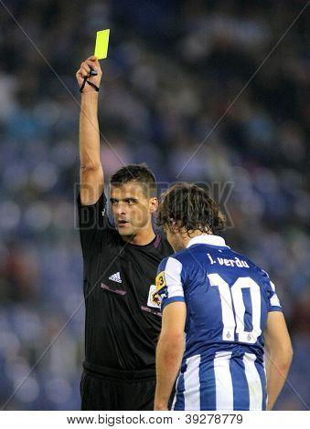 BARCELONA - NOV, 10: Referee Jesus Gil Manzano delivers yellow card during a Spanish League match between Espanyol and Osasuna  at the Estadi Cornella on November 10, 2012 in Barcelona, Spain