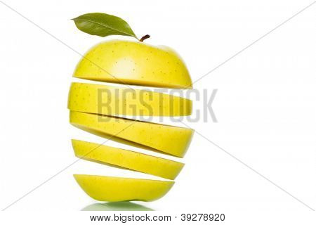 Fresh green golden delicious apple cut into slices floating on top of each other isolated on white background.