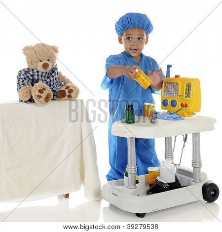 "An adorable preschool ""doctor"" in blue scrubs questioning about the medication he should be giving his patient (toy bear) from his emergency cart.  On a white background."