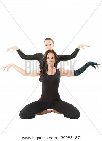 Two Young Women Make Stretch On Yoga Pose On Isolated White Background