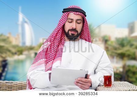 arabian man working on a mobile tablet & drinking tea