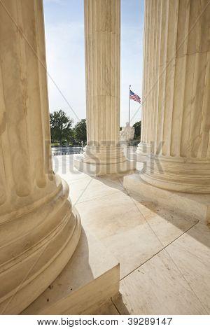 American Flag Viewed Between Pillars Of Supreme Court Building