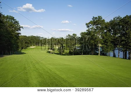 Golf Fairway Lined With Trees Near Lake