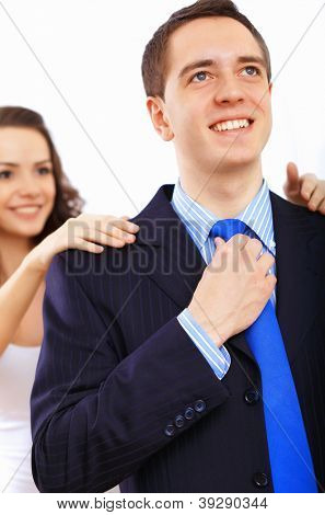Young businessman dressing at home in the morning. Woman helping to fasten his tie