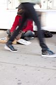NEW YORK - OCT 18: A homeless man in Times Square sits on the sidewalk with a sign that reads 'Pleas