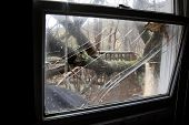 ANDOVER, NJ - OCT 30: A broken window pane from inside a home struck by falling trees after Hurrican