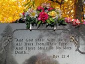 image of revelation  - silk flowers on a cemetery grave tombstone revelations bible verse - JPG