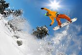 foto of snowboarding  - Snowboarder jumping against blue sky in the high mountains