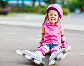 Cheerful roller skater in protective equipment sitting on the ground