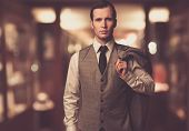 stock photo of mafia  - Man in waistcoat with jacket over his shoulder against blurred background - JPG