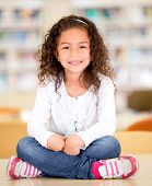stock photo of schoolgirl  - Happy schoolgirl at the library sitting on top of a table - JPG