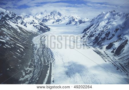 Snowfield in valley between snow-covered mountains