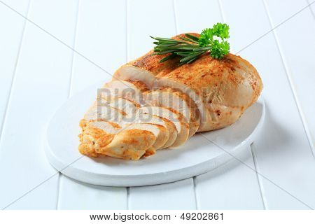 sliced chicken breast with fresh herbs on a cutting board