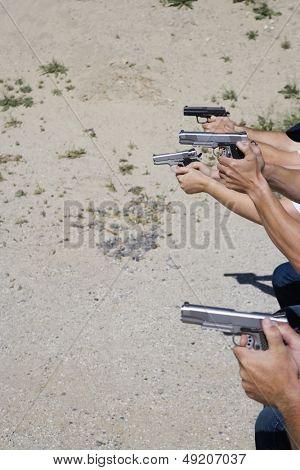 Closeup of hands aiming guns at firing range