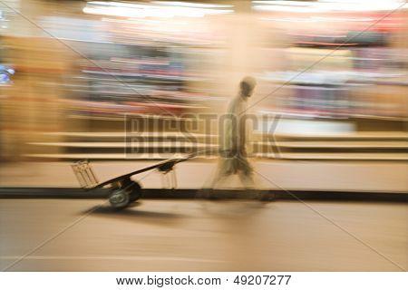 Dubai UAE A man wheels an empty cart through the streets of Deira just after dark.
