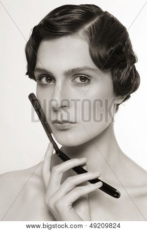 Duotone portrait of beautiful woman with vintage razor in her hand
