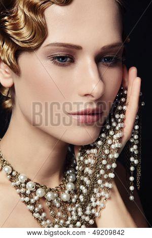 Porträt von schöne junge Frau mit retro-Frisur und ausgefallene Halskette