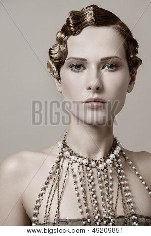 Schöne junge Frau mit retro-Frisur und ausgefallene Halskette