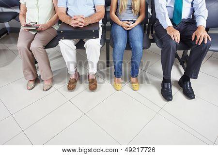 Füße von unterschiedlichen Menschen sitzen in einem Warteraum