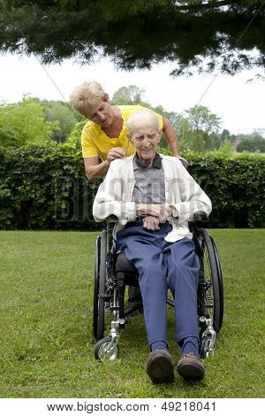 Daughter Showing Concern For Senior Dad In Wheel Chair
