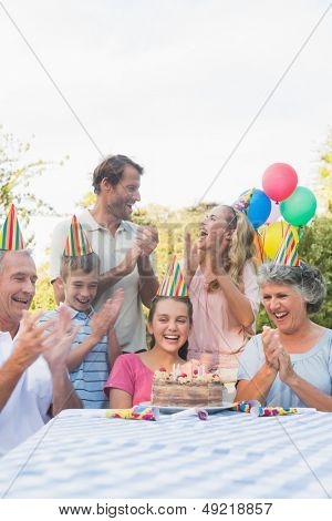 Cheerful extended family clapping for little girls birthday outside at picnic table
