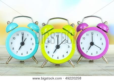 Colorful alarm clocks on table on bright background